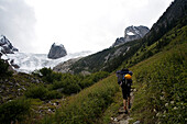 Man carrying a large backpack with a yellow climbing helmet attached to it hikes uphill towards a glacier British Columbia, Canada
