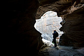Man standing in the light of the entrance to cave Victoria, Australia