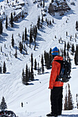 A male snowboarder looks back at a massive cliff he just went off in Utah Salt Lake City, Utah, USA