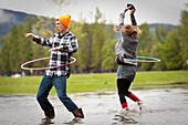 Two young adults dance while hula-hooping in a large puddle Sandpoint, Idaho, USA