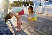 Two little girls are playing football in an alleyway with the sun in background Destin, Florida, USA