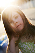 A little girl with long hair is staring at the camera with the sun shining through her hair Destin, Florida, USA