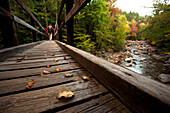 Low angle perspective of one man hiking across a wooden bridge with a stream and fall leaves in view Conway, New Hampshire, USA