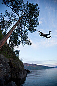 A young adult on a rope swing at sunset in Idaho Sandpoint, Idaho, USA