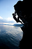 Young man free soloing up a rock with a kayak in the background in Idaho Sandpoint, Idaho, USA