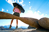 A woman sitting on a natural rock arch holding an umbrella Lone Pine, California, USA