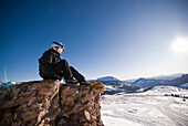 A middle aged woman looks into the distance over a valley of snow in the Rocky Mountains Colorado, USA