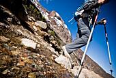 A hiker with trekking poles cross a small stream high on Mt. Kilimanjaro Tanzania