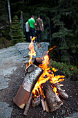 A campfire burns with three young men in the background looking over the edge of the cliff Sandpoint, Idaho, USA