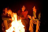 Three women talk and laugh together around a campfire Utah, USA