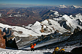 Mountaineer waiting for exhausted team member on summit day on Aconcagua, Mendoza, Andes Mountains, Argentina