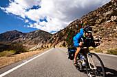 A male cyclist rides a loaded touring bike down the Tioga Pass in Yosemite, California Yosemite, California, United States of America