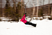 A woman plays on a zip line in Bretton Woods, New Hampshire. Blurred motion Bretton Woods, New Hampshire, United States of America