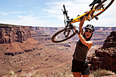 A woman cheers while holding her bike with canyons in the distance Utah, United States