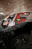 A middle aged woman wearing white tshirt and red pants rock climbing in Jilotepec, Estado de Mexico, Mexico Not applicable, Estado de Mexico, Mexico