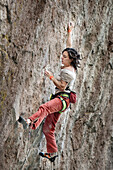 A middle aged woman wearing white tshirt and red pants rock climbing in Jilotepec, Estado de Mexico, Mexico Not applicable, Estado de Mexico, Mexico