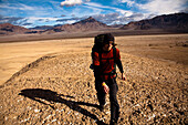 A young man backpacks through the Confidence Hills in Death Valley Nation Park, California Death Valley, California, United States of America