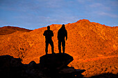 Two silhouetted male backpackers pose for a portrait while standing on a rock pile while hiking through Death Valley's Confidence Hills, California Death Valley, California, United States of America
