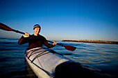 A young man smiles while paddling a touring kayak just outside of Ventura Harbor in Ventura, California Ventura, California, United States of America