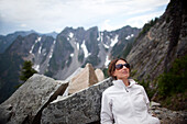 A woman takes a break after hiking to Kendall Katwalk on the Pacific Crest Trail in the Cascade Mountains near Snoqualmie Pass in Kittatas County, Washington State, Washington, USA