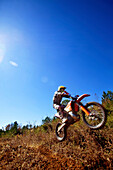 A motorcyclist catches air on a jump during an Enduro race in Maplesville, Alabama. (Back lit, Lens Flare, Motion Blur), Maplesville, Alabama, United States