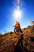 A motorcyclist catches air on a jump during an Enduro race in Maplesville, Alabama. (Back lit, Lens Flare), Maplesville, Alabama, United States