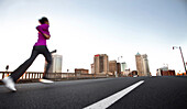 A teenage girl runs on the street away from the camera towards downtown Birmingham, Alabama. (motion blur), Birmingham, Alabama, United States
