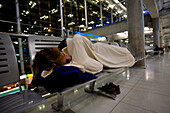 A male traveler sleeps on a bench in the Bangkok International Airport in Bangkok, Thailand Bangkok, Bangkok, Thailand