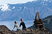 Two young men howl next to a balanced rock stack above a mountain lake in Idaho Sandpoint, Idaho, USA