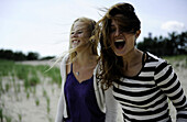 Two women laugh in the wind at the beach Cape Cod, Massachusetts, USA