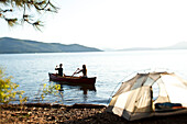 Two young adults canoeing on a camping trip next to a lake in Idaho Sandpoint, Idaho, USA