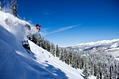A athletic snowboarder jumping off a cliff on a sunny powder day in Colorado Vail, Colorado, USA