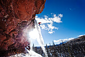A athletic skier jumping off a cliff in the backcountry on a sunny day in Colorado Vail, Colorado, USA