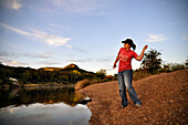 A young woman playfully throws rocks into a river at sundown