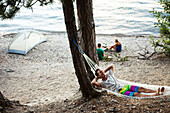 A group of young adults camping laugh and smile next to a lake Idaho., Sandpoint, Idaho, USA
