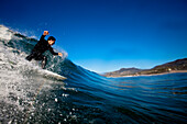 A male surfer sets up for a backside barrel while surfing at Zuma Beach in Malibu, California., Malibu, California, United States of America