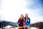 Two young women laugh and smile while hiking in the snow on a beautiful winter day in Idaho., Sandpoint, Idaho, USA