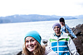 A group of three young adults smile while hiking at the edge of a lake in Idaho., Sandpoint, Idaho, USA