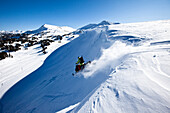 A snowmobiler jumping off a cornice on a sunny winter day in Montana., Bozeman, Montana, USA