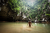 A athletic young man adventuring deep into a remote jungle pool stands naked in Thailand., Railay, Thailand