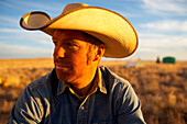 A cowboy smiles with the warm rays of the setting sun following a dusty day in the saddle., Arizona, USA