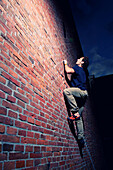 A climber scales an old brick wall in Groningen, the Netherlands., Groningen, Groningen, The Netherlands