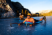 An ice climber works his way across Tenaya Lake in Yosemite, California while getting a belay from a fellow climber in a pool raft., Yosemite, California, United States of America