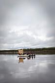 Group of boys in rafts using a tarp as a sail with a tilt shift lens., Kotzebue, AK, USA