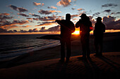 Three male surfers check the surf conditions at sunset during a surf trip in Central Baja, Mexico., Central Baja, Baja California, Mexico