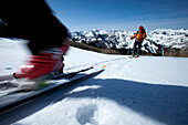 Low angle perspective of a skier's boot motion blurred with a skier int he background., Park City, Utah, USA