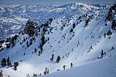 Two backcountry skiers hiking up a mountain with big mountains in the background., Ogden, Utah, USA