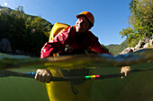 Split level view of one man smiling and doing a bow stall in his kayak., Fayetteville, WV, USA