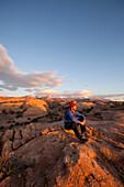 Young man hiking on slickrock near Moab, Utah., Moab, Utah, USA