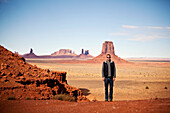 A man poses for a picture among the rock formations of Monument Valley on the Utah/Arizona border., Kayenta, AZ, USA